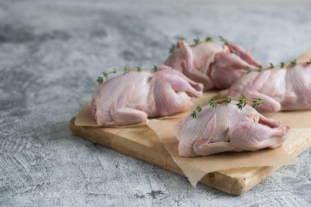 Raw uncooked quail. raw meat quails ready for cooking on a cutting board with copy space/