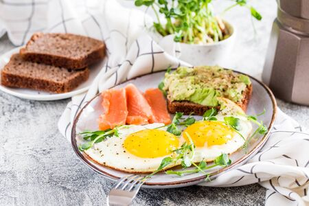 Egg breakfast. Healthy nutritious breakfast with eggs, salmon, avocado sandwich and sprouted pea seeds. Foto de archivo - 140556404