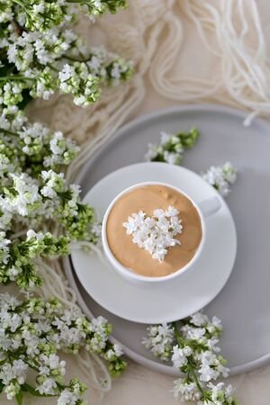 Composition with the branches of lilac and fresh coffee with foam in white cup. Relax time, pay yourself first