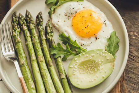 Healthy homemade breakfast with asparagus, fried egg, avocado and arugula. quarantine healthy eating concept. keto diet