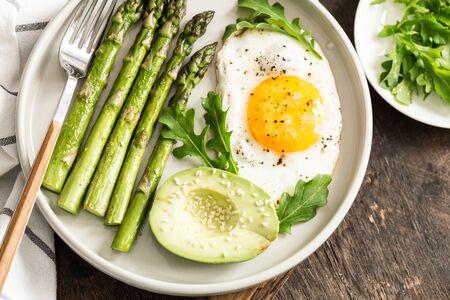 Gesundes hausgemachtes Frühstück mit Spargel, Spiegelei, Avocado und Rucola. Quarantäne-Konzept für gesunde Ernährung. Keto-Diät