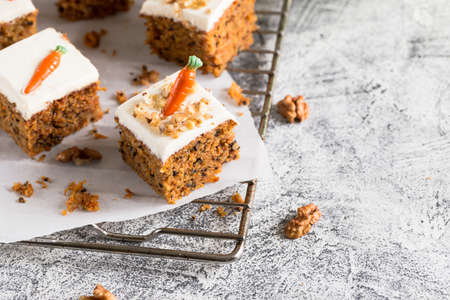 pieces of carrot cake with walnuts with icing cream on a light background. tinting. selective focus /