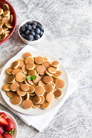 Tiny pancakes for breakfast. Cereal pancakes with blueberries, bananas, strawberries on gray background. Trendy food. Copy space for text or design Zdjęcie Seryjne