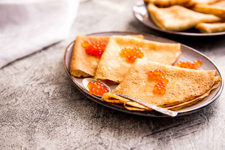 Traditional Russian pancakes with red caviar. Fried crepes with caviar and sour cream