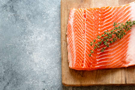 Salmon. Fresh raw salmon fish fillet with cooking ingredients, herbs and lemon. Close up. healthy food, diet or cooking concept