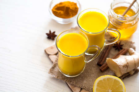Turmeric tea drinks with milk and honey for beauty and health. Spicy healthy haldi