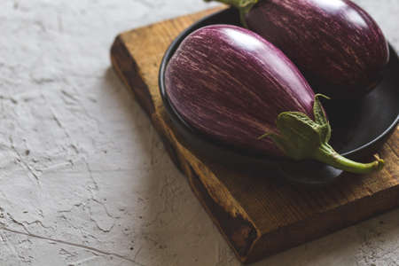 fresh ripe eggplants on a cutting board on a concrete gray background