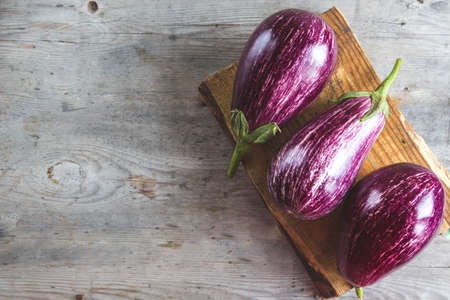 fresh ripe eggplants on a cutting board on a wooden gray background 스톡 콘텐츠