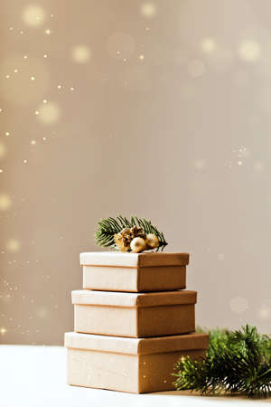 Brown gift boxes. Stacks of Christmas presents with Christmas tree. copy space with defocused lights
