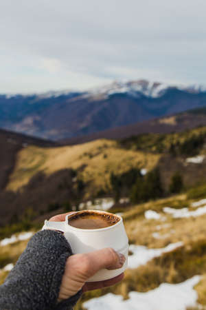 tourist cup with hot drink in woman hands overlooking mountain landscape