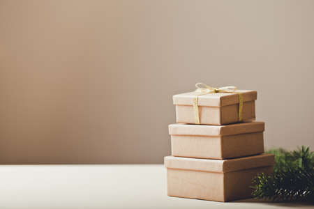 Brown gift boxes. Stacks of Christmas presents with Christmas tree. copy space /