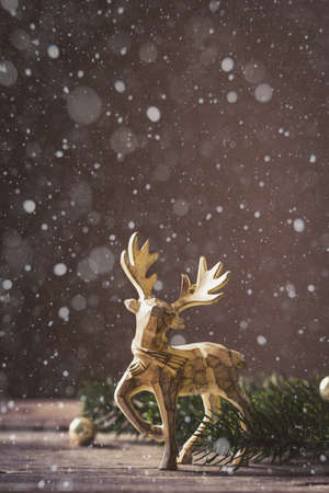 Christmas card conception. Christmas toy deer decoration with christmas tree branch and snow