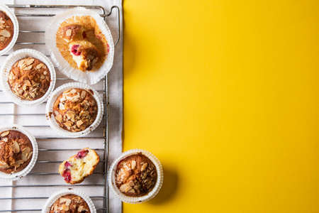homemade muffins on a baking rack on a yellow background. place for your text, flat lay Archivio Fotografico