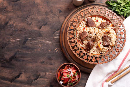 The concept of oriental cuisine. Traditional asian dish - pilaf from rice, vegetables and meat in a plate on a wooden table. background image. top view, copy space, flat lay Archivio Fotografico