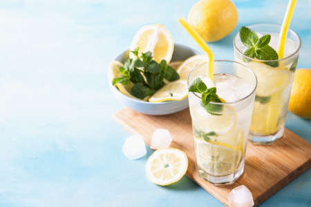 Two glass with lemonade or mojito cocktail with lemon and mint, cold refreshing drink or beverage with ice on blue background. Copy space.