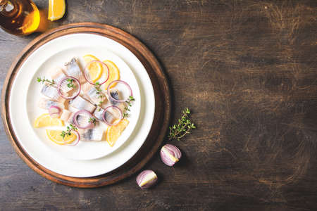 Salted herring with spice, herbs and onion on plate on wooden background with copy space. Marinated sliced fish. Food with healthy unsaturated fats, Omega 3. Top view, flat lay Archivio Fotografico