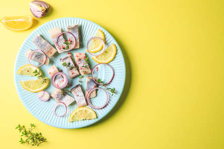 Salted herring with spice, herbs and onion on plate on yellow background with copy space. Marinated sliced fish. Food with healthy unsaturated fats, Omega 3. Top view, flat lay