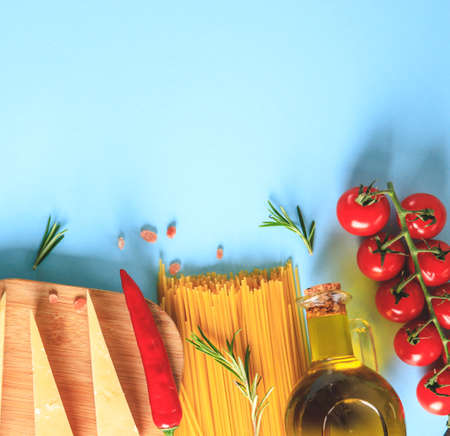 Uncooked pasta on blue background. Top view. Raw pasta with ingredients for cooking. Food concept. Italian food.