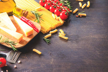 Uncooked pasta on wooden background. Top view. Raw pasta with ingredients for cooking. Food concept. Italian food.