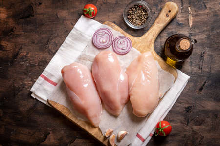 raw chicken breasts on a cutting board and wood background with onion and garlic. Archivio Fotografico