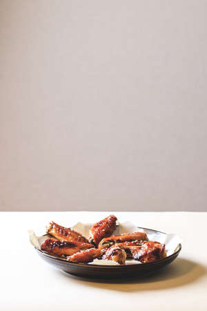 baked chicken wings with crispy crust on plate and trending beige background.