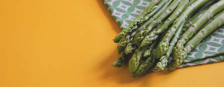 Asparagus. Fresh Asparagus. Pickled Green Asparagus. Bunches of green asparagus on yellow. Archivio Fotografico