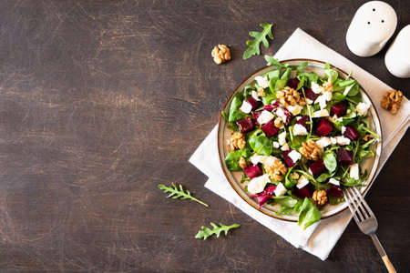 Beet or beetroot salad with fresh arugula, soft cheese and walnuts on plate, dressing and spices on dark wooden background, copy space, top view /