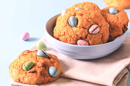 homemade cookies chocolate chips with colored candy eggs on a blue background.