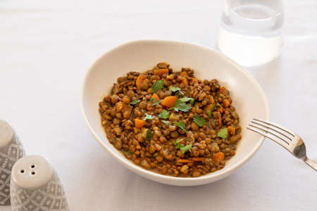lentils with vegetables in a plate on the dining table. comfort homemade food, vegetarian lentils. Archivio Fotografico