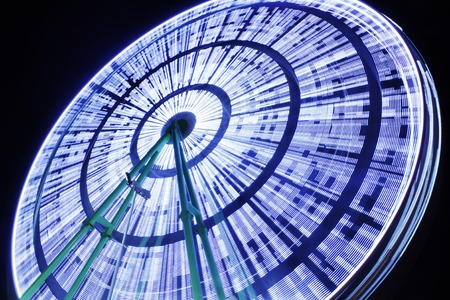 Amusement park at night - ferris wheel and rollercoaster in motion Stock Photo