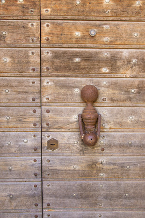 view of a wooden doorway: Knocker to knock on an old wooden door