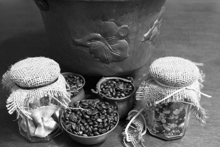 expressed: Coffee beans or seeds in copper bowls with noodles and vegetables in glass jars with caps in jute and copper pot on the bottom.