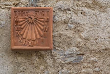 reloj de sol: Sundial in clay attached to the wall with Latin inscription Foto de archivo