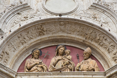 lazarus: Depiction of three statues on the top of the door of a church in Montepulciano Stock Photo