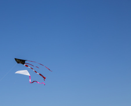 Kite hit from the Sun on a background of blue sky Stock Photo
