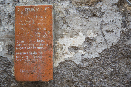 Red brick attached vertically to the wall with the written partially illegible on the surface