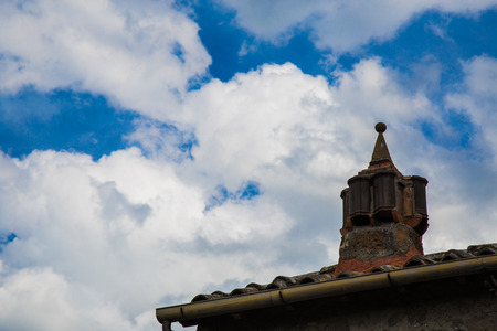 tall chimney: Chimney of a fireplace handcrafted masonry above the roof of a house Stock Photo