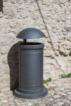 wastebasket: Metal waste container behind a stone wall. Stock Photo