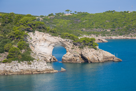 Natural arch carved into the cliff in the Gargano