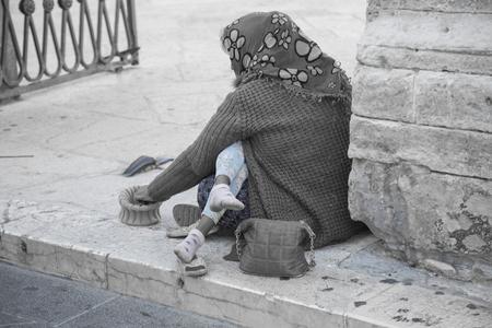 教会の入り口の前に彼女の腕の子供の乞食 写真素材