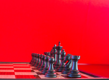 Seen blacks chess surface and cut with a red background. Stock Photo