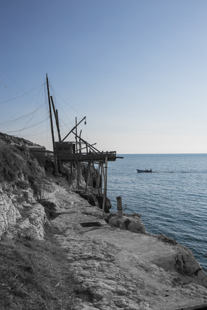 Trabucco on the cliff and boats returning after fishing