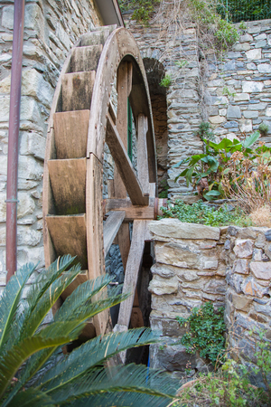 Wheel of wooden waterwheel attached to a stone wall.