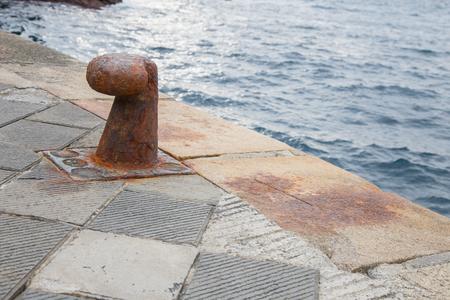 ship anchor: Rusty bollard for mooring of boats.