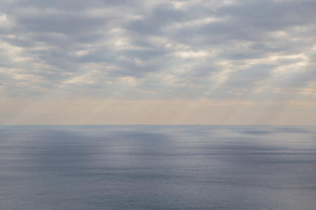 The Ligurian Sea panorama with the suns rays that penetrate through the clouds. Stock Photo