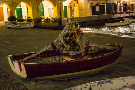 Small fishing boat with a Christmas tree inside.