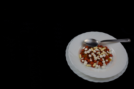 Medicinal colored pills and ova gel in a white ceramic plate with spoon.