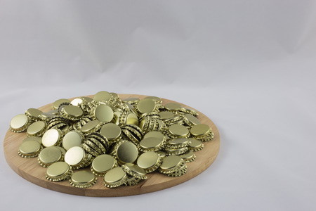 Pile of cans to close the bottles on a wooden tray with white background.