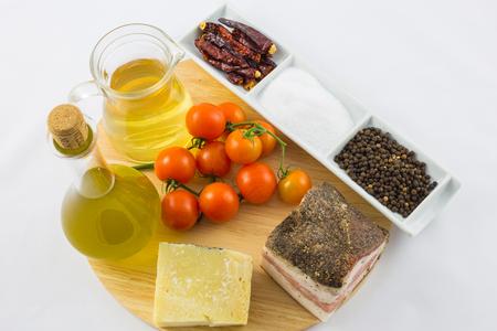 Gli ingredienti per la pasta Amatriciana, tra cui pancetta, formaggio, pomodoro, pepe e peperoncino. Archivio Fotografico - 83168331