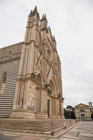 Side Perspective of the facade of Orvieto Cathedral.The Cathedral of Orvieto is the cathedral of the Diocese town, Italian Gothic architecture. The facade is decorated by a large number of bas-reliefs and sculptures Stock Photo